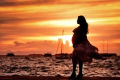 Pregnant Woman Standing Near Seashore during Sunset Royalty Free Stock Photos