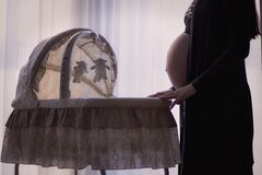 Pregnant Woman Standing Near White Brown Bassinet Stock Image