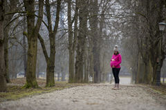 Pregnant woman standing outside in a park Stock Photos