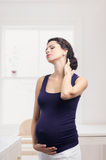Pregnant woman standing with a pain in the neck. This image has attached release stock images