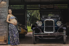 Pregnant Woman Standing Beside Post Near Classic Car at Daytime Royalty Free Stock Photo