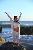 Pregnant woman standing on a rock at the beach. With hands raised Stock Photography