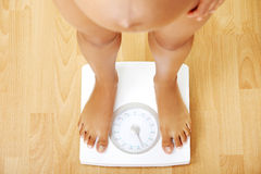 Pregnant woman standing on the scales. Stock Image