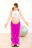 Pregnant woman standing on weight scale at home Stock Photo