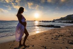 Pregnant woman stands on the beach during sunset time. Pregnant woman with a white dress and free belly stands on the beach during sunset time royalty free stock images