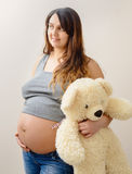 Pregnant woman stands holding a white teddy bear Royalty Free Stock Photography