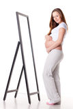 Pregnant woman stands before mirror. Royalty Free Stock Images