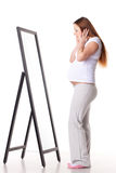 Pregnant woman stands before mirror. Royalty Free Stock Image