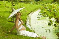 Pregnant woman stands near a lake with lotuses Royalty Free Stock Images