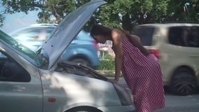 A pregnant woman stands near a wrecked car on a rural road. Upset girl does not know what to do with the breakdown. A pregnant young woman stands near a wrecked stock video