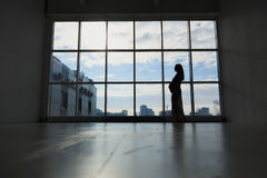 Pregnant woman stands by the window. Silhouette against the sky Stock Photography