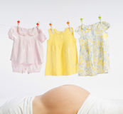 Pregnant woman. Stomach and baby dresses hanging on the rope Royalty Free Stock Photos