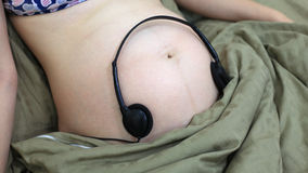 Pregnant woman stomach with headphones listening to music Royalty Free Stock Photography