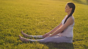 Pregnant woman stretching at the grass stock video footage