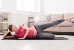 Pregnant woman stretching legs training indoors. Pregnant woman stretching legs training at home, copy space. Expectant female makes warmup aerobics exercise Stock Image