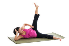 Pregnant woman stretching on mat Royalty Free Stock Image