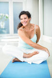 Pregnant woman stretching while sitting on exercise mat Royalty Free Stock Photography