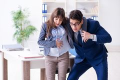 Pregnant woman struggling in the office and getting colleague he royalty free stock photos