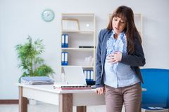 The pregnant woman struggling to do work in office. Pregnant woman struggling to do work in office Royalty Free Stock Images