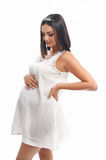Pregnant woman in the studio. Over white. Royalty Free Stock Image