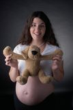 Pregnant woman and stuff dog. Seven month pregnant woman holding stuff toy dog by the arm Stock Photos