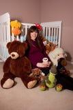 Pregnant woman with stuffed toys Stock Photos