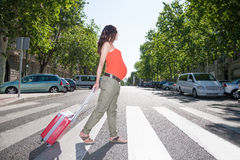 Pregnant woman with suitcase in crosswalk Royalty Free Stock Image