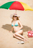 Pregnant woman sunbathing on sandy beach Stock Photo