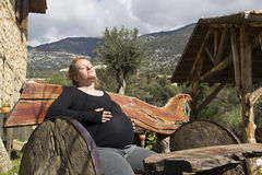 Pregnant woman sunbathing on wooden bench Stock Images