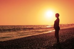 Pregnant woman and sunset. And sea royalty free stock images