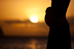 Pregnant woman at sunset. Pregnant woman standing on the beach at sunset stock images