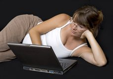 Pregnant woman surfing the net. Pregnant woman lying down surfing the web on a laptop stock photos