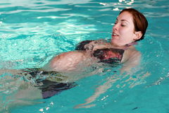 Pregnant woman swimming Stock Image