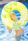 Pregnant woman is swimming with green rubber ring Royalty Free Stock Photography
