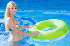 Pregnant woman is swimming with green rubber ring Royalty Free Stock Images