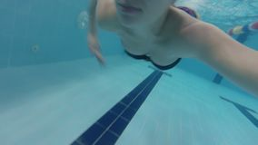 Pregnant woman swims underwater in the pool. Underwater view of pregnant woman swimming in the pool. Healthy pregnancy. Underwater video of young pregnant woman stock video footage