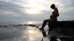 Pregnant woman in a swimsuit sitting in profile cradling her swollen belly stock video footage