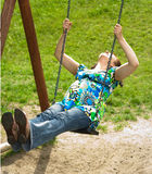 Pregnant woman on swing. Pregnant woman on the playground Royalty Free Stock Photo