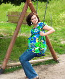 Pregnant woman on swing. Pregnant woman on the playground Stock Photography