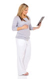 Pregnant woman tablet computer. Side view of pregnant woman using tablet computer on white background Stock Photos