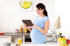 Pregnant woman with tablet pc eating at home Royalty Free Stock Photos