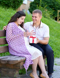 Pregnant woman takes a gift from her husband, happy family, couple in city park, summer season, green grass and trees Royalty Free Stock Images