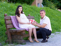 Pregnant woman takes a gift from her husband, happy family, couple in city park, summer season, green grass and trees Royalty Free Stock Photography