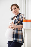 Pregnant Woman Taking Break Whilst Decorating Nursery Stock Images