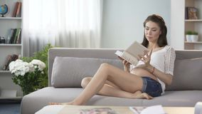 Pregnant woman taking photo album to look at pictures, family circle, genealogy
