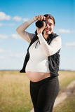 Pregnant woman taking photo with camera Royalty Free Stock Photos