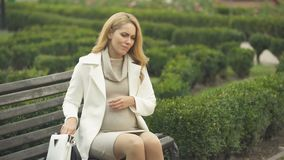 Pregnant woman taking pill, suffering headache, sitting on bench, migraine stock footage