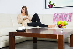 Pregnant woman taking pills. On sofa Royalty Free Stock Image