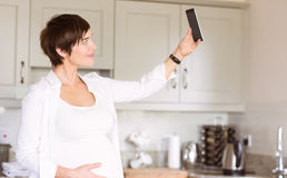 Pregnant woman taking a selfie Stock Image