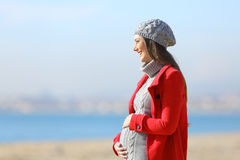 Pregnant woman taking a walk on the beach Royalty Free Stock Photo